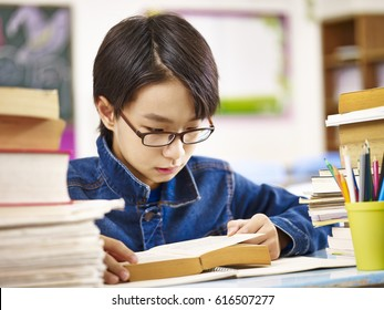 asian elementary school boy wearing glasses reading a thick book.