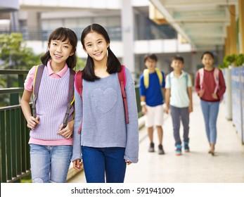 asian elementary school girls walking in classroom building.
