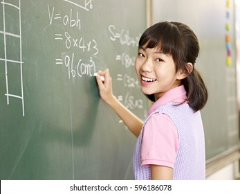 asian elementary schoolgirl looking at camera smiling while solving a math problem.