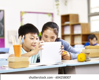 asian elementary schoolgirl and school boy using tablet computer together in classroom.