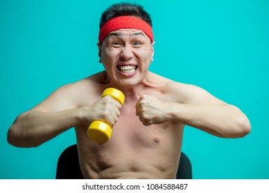 Asian emotional man with naked torso exercising with dumbbells screaming from efforts showing strong motivation to phisical health and fitness body