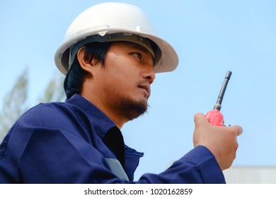 Asian engineer in blue safety uniform and white security helmet using walkie-talkie on blurred industry plant and blue sky background for industrial concept