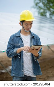 Asian engineer checking solar panel setup with tablet