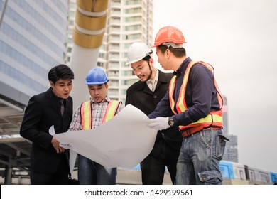 Asian engineer man and construction workers discussing on blueprint plan building project in the modern building city, teamwork and business concept