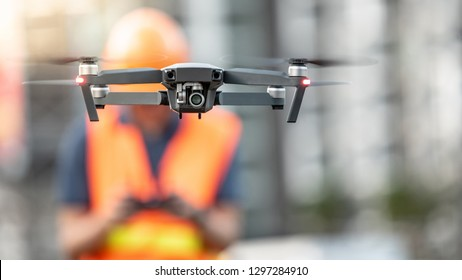 Asian engineer man or male worker flying drone over construction site. Using unmanned aerial vehicle (UAV) for land and building site survey in civil engineering project.