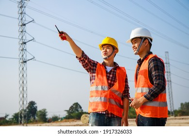 Asian engineer manager and foreman or leader discussion and pointing to construction site project on workplace and High voltage power line pylon in the background. Teamwork, Leadership concept.
