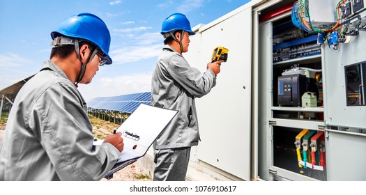 Asian engineer opens electric box to check photovoltaic power generation