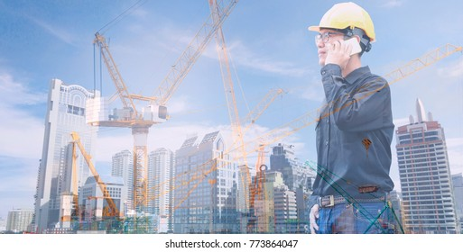 Asian engineer is talking smart phone with business office building and crane construction background.