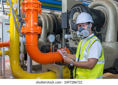 Asian engineer wearing glasses working in the boiler room,maintenance checking technical data of heating system equipment,Thailand people Wearing a gas mask