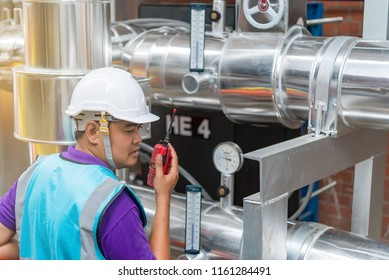 Asian engineer wearing glasses working in the boiler room,maintenance checking technical data of heating system equipment,Thailand people