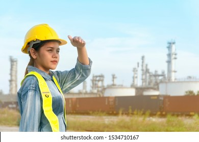 Asian engineer woman looking Successful with her job. Asian woman architect looking at the distance to lead to success with yellow helmet and jean shirt. Concept Engineer and business work.