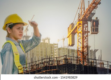 Asian engineer woman looking Successful with her job. Asian woman architect looking at the distance to lead to success with yellow helmet and jean shirt duplicate photo.Concept Engineer and civil work