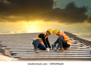 Asian engineer workers install new CPAC roof, roofing tools, electric drill, use on new roof with CPAC roof house construction idea.