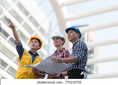 Asian engineers group consult construction on site building working while holding blueprint paper. in city background. teamwork concept