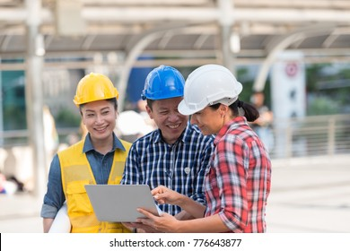 Asian engineers group consult construction on site building working while holding laptop and blueprint paper. in city background. teamwork concept