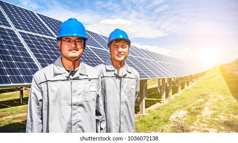 Asian engineers guarding solar photovoltaic panels under the hot sun