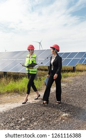 Asian engineers inspect the photovoltaic area.