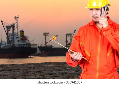 Asian engineers thinking and holding the note pad on port city at sunset time, transportation industrial concept