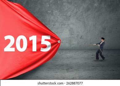 Asian entrepreneur woman try to drag number 2015 on a big banner