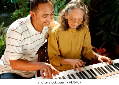 asian ethnic elderly woman play piano together with young adult male