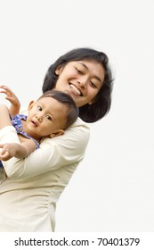 Asian ethnic family portrait of working mom embrace her little daughter