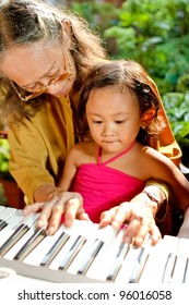 asian ethnic grandmother teach child playing piano