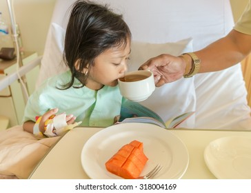 Asian Ethnic Little Girl Patient in Hospital Drinking Tea Helped by Her Father