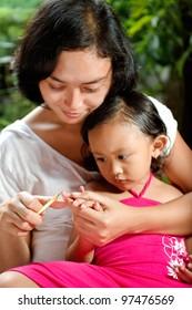 asian ethnic mom cutting little girl fingernail