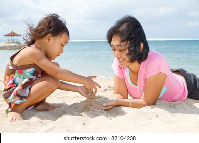 asian ethnic mother and child playing with white sand on tropical beach