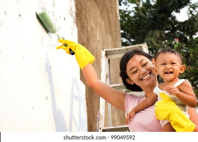 asian ethnic mother happy painting house together with child