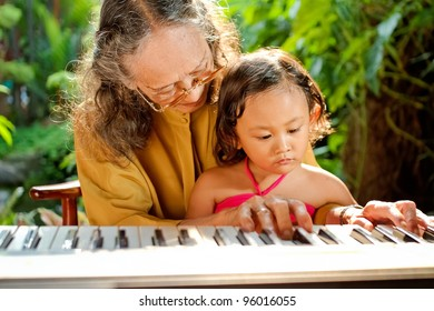 asian ethnic old female teaching child play piano