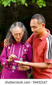 asian ethnic senior woman taking pills helped by young adult son