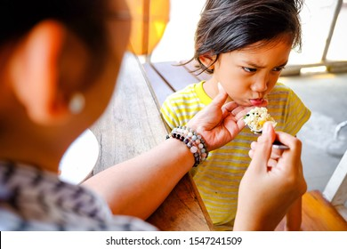 Asian Ethnicity Boy Showing Cranky Facial Expression while Being Feed Lunch Meals by His Mother in A Restaurant
