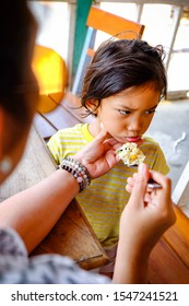 Asian Ethnicity Child Showing Cranky Facial Expression while Being Feed Lunch Meals by His Mother in A Restaurant. Seems He Doesn't Like It's Taste