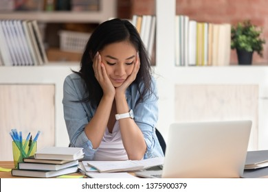 Asian ethnicity student girl sitting at table full with books textbooks educational materials looking at summary copybook feels exhausted and bored, loaded with tasks work study deadline exams concept