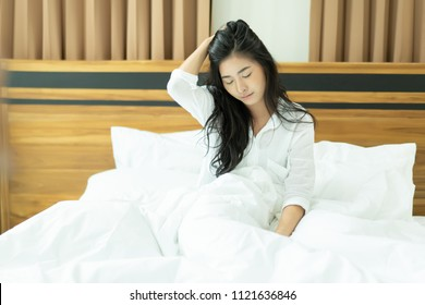 Asian Exhausted sleepy young woman on bed with messy hair, feeling drowsy after wake up early in morning, sleepless last night.Tired asia insomnia girl,non sleep,Depressed people put head in hand