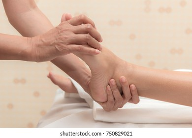 Asian exotic holiday spa concept. Beautiful young white woman enjoy relaxing during foot massage at spa, taken indoor in real spa location.
