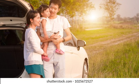 Asian families are happy outside the car.