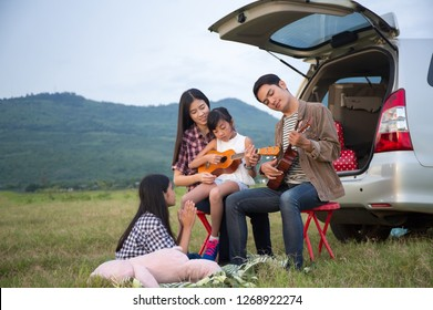 Asian families are happy outside the car.  Asian family