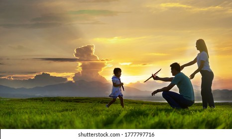 Asian families are happy in the wide fields after sunset.