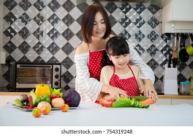 Asian Families : little girl helping her mother prepare food in the kitchen.