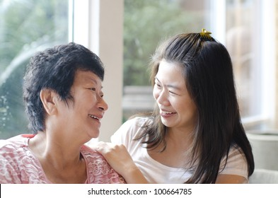 Asian family, adult daughter having conversation with senior mother indoor.