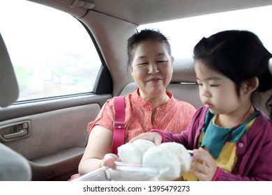 The Asian family in the back seat of car.