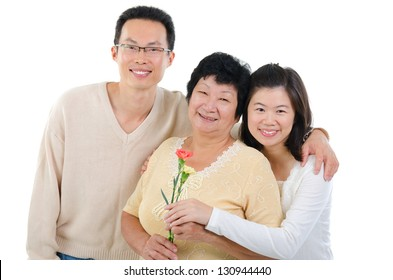 Asian family celebrates Mothers Day. Adult offspring giving carnation flowers to senior mother isolated on white.