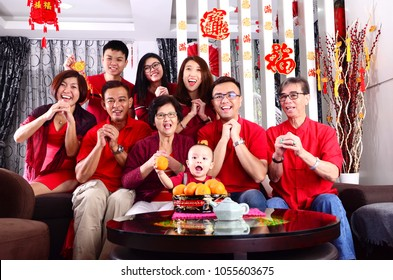 """Asian family celebrating chinese new year. Chinese characters in the photo means """"wealthy and prosperous"""""""