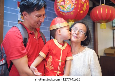 Asian family celebrating Chinese new year, Cute little 2 years old toddler boy in traditional red Chinese suit with his father and grandmother, grandchild kissing grandparent, Lunar New Year concept