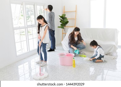 asian family clean a room, asian children learning to clean her house with her mother and her father,  they feeling happy and fun, family activity