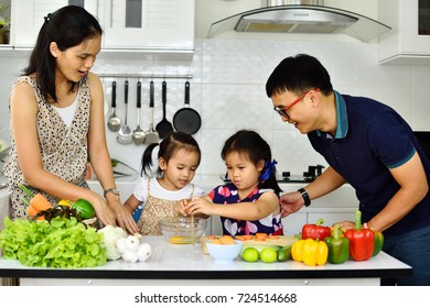 Asian family cooking together in kitchen