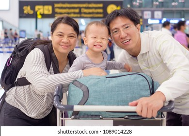 Asian family with cute 18 months / 1 year old toddler baby boy child in airport before boarding at the public Airport, Family travel, vacation with kid concept