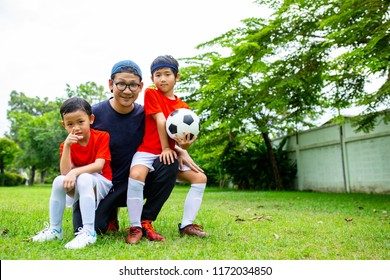 Asian family do activity soccer in the outside together.